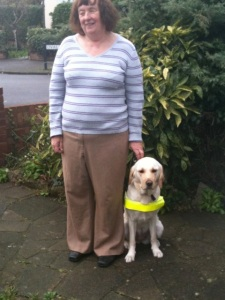 A woman with a white guide dog sat on her left