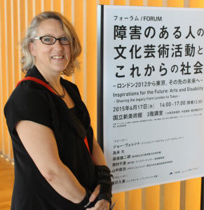 Woman smiling and standing next to a sign with Japanese characters